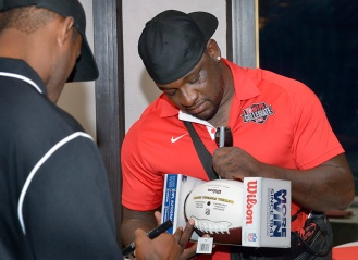 NFL players Kenny Clark and Matthew Hatchette signing authentic NFL footballs.
